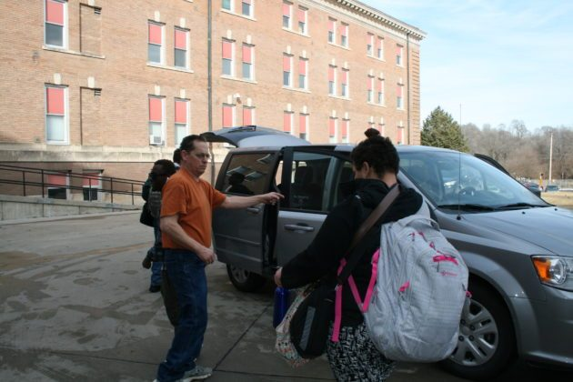 Residential counselor and student prepare to board school van.