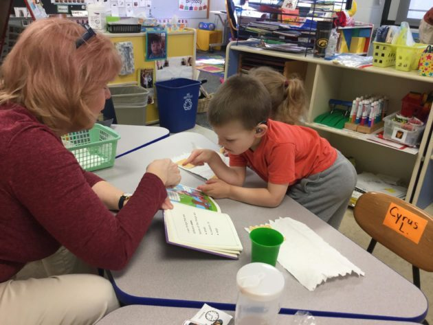 Preschool child reads a book with guidance of teacher.