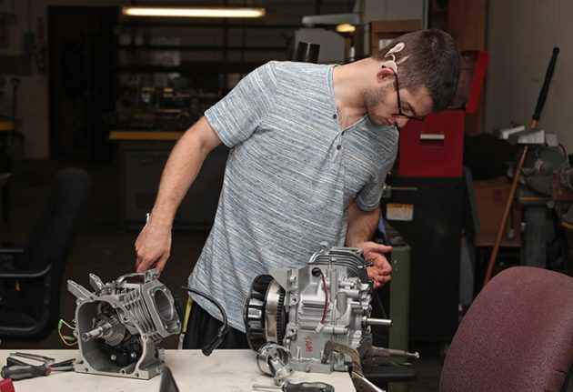 High school boy studies engine in metals tech shop.