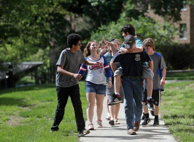 Group of high school students walking on sidewalk, engaging with one another.