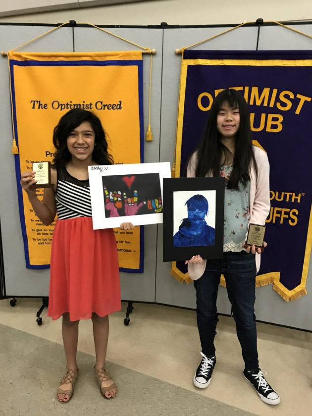 Two girls hold their artwork and awards.